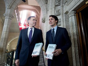 Minister of Finance Bill Morneau walks with Prime Minister Justin Trudeau before tabling the budget. About one in 10 respondents who identify as Liberals said they were less likely to vote Liberal on account of the budget.
