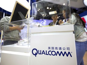 FILE - In this Thursday, April 27, 2017, file photo, visitors look at a display booth for Qualcomm at the Global Mobile Internet Conference (GMIC) in Beijing. On Monday, March 12, 2018, President Donald Trump blocked Singapore-based Broadcom's takeover of U.S. chipmaker Qualcomm on national security grounds.