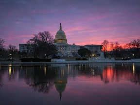 FILE - In this Feb. 6, 2018, file photo, dawn breaks over the Capitol in Washington. The once bipartisan drive to curb increases in health care premiums has devolved into a partisan struggle with escalating demands by each side. It's unclear they'll be able to reach an agreement. And the two parties may end up blaming each other this fall as states announce next year's inevitably higher insurance rates _ just weeks before Election Day on Nov. 6.