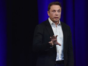 """Tesla CEO Elon Musk, in a testy Twitter exchange, said he is """"back to sleeping at the factory"""" while trying to fix production delays with the Model 3 electric car."""