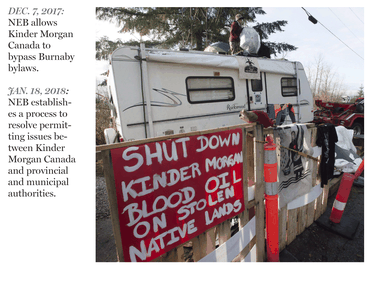 A protester stands on top of a trailer outside the main gates of Kinder Morgan in Burnaby.