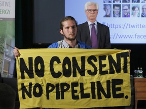 """Trans Mountain Pipeline protester Gabriel D'astous interrupts a speech by Natural Resources Minister Jim Carr at the """"Positive Energy"""" conference at the University of Ottawa on April 23, 2018."""