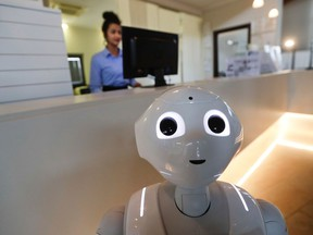 In this photo dated March 12, 2018, robot Robby Pepper stands at the front desk of hotel in Peschiera del Garda, northern Italy, Monday, March 12, 2018. Robby Pepper, billed as Italy's first robot concierge, has been programed to answer simple guest questions in Italian, English and German, the humanoid, speaking robot will be deployed all season at a hotel on the popular Garda Lake to help relieve the desk staff of simple, repetitive questions.
