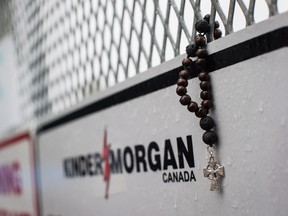 Rosary beads are seen on a gate at Kinder Morgan's facility in Burnaby, B.C., as religious leaders and more than 100 members of diverse faith communities protested against the expansion of the Trans Mountain pipeline.