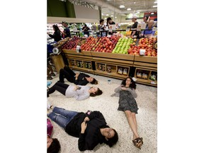 """Demonstrators lie on the floor at a Publix Supermarket in Coral Springs, Fla., Friday, May 25, 2018. Students from the Florida high school where 17 people were shot and killed earlier this year did a """"die in"""" protest at a supermarket chain that backs a gubernatorial candidate allied with the National Rifle Association. Shortly before the the """"die-in"""" Publix  announced that it will suspend political donations."""