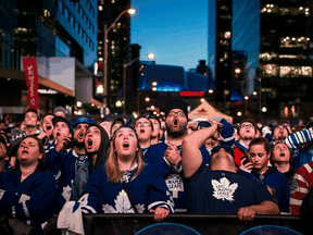 Fans at Maple Leaf Square in Toronto cheer their team.