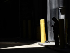FILE- In this June 6, 2017, file photo, a man checks his phone in an alley in downtown Chicago. A security researcher says a website flaw at a U.S. company could have allowed anyone to pinpoint the location of nearly any cellphone in the United States. The lapse at LocationSmart, a company that gathers real-time data on cellular wireless devices, is the latest to highlight how little protection consumers have from trafficking in data about their location.