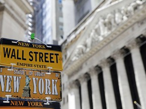 FILE- In this April 26, 2018, file photo, a sample of license plates for sale at a souvenir stand are shown in front of the New York Stock Exchange on Wall Street in the Financial District. The U.S. stock market opens at 9:30 a.m. EDT on Friday, May 18.