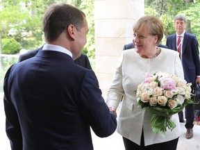 Russian Prime Minister Dmitry Medvedev, left, greets German Chancellor Angela Merkel during their meeting at Putin's residence in the Russian Black Sea resort of Sochi, Russia, Friday, May 18, 2018. The meeting in Sochi is Merkel's first visit to Russia in a year and comes amid tense relations between Berlin and Moscow.