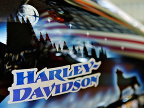 An American flag is reflected in the gas tank of a 2006 Roadking Custom in the showroom of Harley-Davidson of New York.