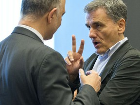 Greek Finance Minister Euclid Tsakalotos, right, speaks with European Commissioner for Economic and Financial Affairs Pierre Moscovici during a meeting of eurogroup finance ministers at EU headquarters in Luxembourg on Thursday, June 21, 2018. Eurozone nations are working on the final elements of a plan to get Greece successfully out of its eight-year bailout program and keep its massive debt burden manageable.