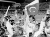 Pakistan's cricket captain, Imran Khan, waving a Pakistan flag, is cheered by his teammates after Pakistan defeated England in the World Cup Cricket final in Melbourne, Australia, in March 1992.