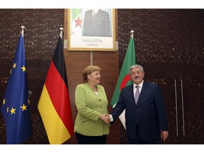 German Chancellor Angela Merkel shakes hands with Algerian Prime Minister Ahmed Ouyahia ahead of talks in Algiers, Monday Sept.17, 2018. Merkel is visiting Algeria for a day to promote bilateral ties and discuss migration and the situation in neighboring Libya.