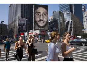 FILE - In this Sept. 6, 2018, file photo, people in New York walk past a Nike advertisement featuring former San Francisco 49ers quarterback Colin Kaepernick, known for kneeling during the national anthem to protest police brutality and racial inequality. In response to Nike's support of Kaepernick, the Rhode Island town of North Smithfield is considering asking its departments to refrain from purchasing Nike products.