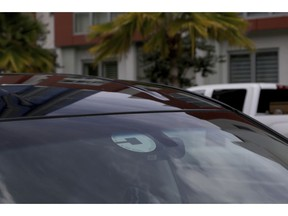 FILE- In this June 6, 2018, file photo Uber driver Joshua Oh drives in Honolulu. Uber has created a feature on its app to reach out to passengers and drivers if it detects an accident or unplanned stop. Drivers will also have access to a hands-free feature to pick up passengers without touching their phones, and they will no longer see data detailing where they retrieved passengers in the past.