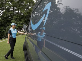 """FILE- In this June 27, 2018, file photo, Parisa Sadrzadeh, a senior manager of logistics for Amazon.com, opens the door of an Amazon-branded delivery van at the request of a photographer in Seattle, following a media event for Amazon to announce a new program that lets entrepreneurs around the country launch businesses that deliver Amazon packages. Amazon says it has ordered 20,000 vans for its new delivery program. The online retailer says """"tens of thousands"""" of individuals have applied for the program, and it had to up its van order to 20,000 from 4,500."""