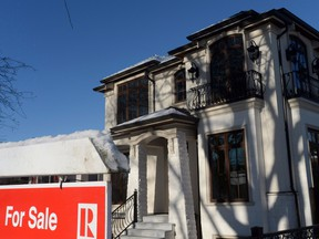 A for sale sign is shown outside a house in Vancouver. Prospects for the city's housing market, which has some of the most expensive homes in the world, has grown more precarious, according to a analyst poll.