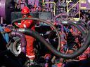 A worker adjusts hoses during a hydraulic fracturing operation at a gas well.