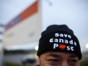 """A postal worker wears a """"Save Canada Post"""" hat during a Canadian Union of Postal Workers (CUPW) strike in front of the Gateway Postal facility in Toronto."""