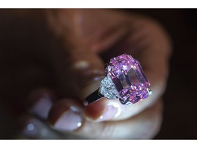 """FILE - In this Thursday, Nov. 8, 2018 file photo, a Christie's employee displays an 18.96-carat fancy vivid pink diamond during a preview at Christie's in Geneva, Switzerland.  Christie's sold the """"Pink Legacy"""" diamond at auction Tuesday, Nov. 13 for more than $50 million including fees, saying it's a new world record price per carat for a pink diamond. Christie's said that renowned jeweler Harry Winston was the buyer."""