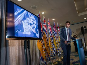 B.C. Attorney General David Eby speaks as a video is shown of bundles of cash brought to a casino by a person, after releasing an independent review of anti-money laundering practices during a news conference in Vancouver, on Wednesday June 27, 2018.