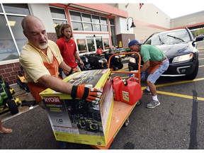 FILE - In this Sept. 10, 2018 file photo, Jim Craig, David Burke and Chris Rayner load generators as people buy supplies at The Home Depot in Wilmington, N.C. Home Depot Inc. reports earnings Tuesday, Nov. 13.
