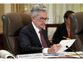 FILE- In this Oct. 31, 2018, file photo Federal Reserve Chair Jerome Powell looks over papers as the Federal Reserve Board holds a meeting at the Marriner S. Eccles Federal Reserve Board Building in Washington. With the economy strong, wages rising and unemployment at a near-five-decade low, the Federal Reserve remains on track to keep raising interest rates, just not this week. After the Fed's latest policy meeting, it's expected to signal a healthy outlook for the economy but to hold off on any further credit tightening, most likely until December. A rate hike in December would mark the fourth this year.