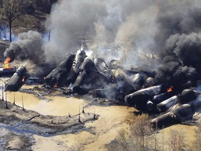 FILE- In this Nov. 8, 2013 file photo, a tanker train carrying crude oil burns after derailing in western Alabama outside Aliceville, Ala. The Trump administration vastly understated the potential benefits of installing more advanced brakes on trains that haul explosive fuels when it cancelled a requirement for railroads to begin using the equipment. A government analysis used by the administration to justify the cancellation omitted up to $117 million in potential reduced damages from using electronic brakes. Department of Transportation officials acknowledged the error after it was discovered by The Associated Press during a review of federal documents but said it would not have changed their decision.