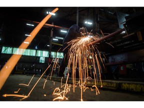 Fabricator Mike Caldarino uses a grinder on a steel stairs being manufactured for a high school in Redmond, Wash., at George Third & Son Steel Fabricators and Erectors, in Burnaby, B.C., on March 29, 2018.