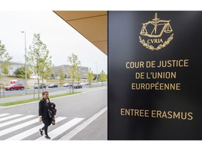 In this photo taken on Monday, Oct. 5, 2015 a woman walks by the entrance to the European Court of Justice in Luxembourg. The European Union's top court ruled Monday, Dec. 10, 2018, that Britain can change its mind over Brexit, boosting the hopes of people who want to stay in the EU that the process can be reversed.
