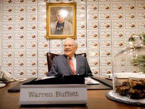 Warren Buffett sits behind a desk under a portrait of founder Mary See at the See's Candies booth during part of the 2016 Berkshire Hathaway AGM.