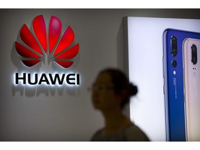 """FILE - In this July 4, 2018, file photo, a shopper walks past a Huawei store at a shopping mall in Beijing. Canada's national game _ brought to you by China's Huawei. As a feud deepens between Beijing and Ottawa over the telecom giant, the company's sponsorship of the flagship """"Hockey Night in Canada"""" broadcast raised questions about its involvement in a beloved national institution."""