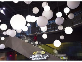 A woman leaves the Cineplex theatre in Toronto on Friday, November 4, 2016. Cineplex Inc. says it had $27.2 million of net income in the fourth quarter, down from $28.8 million a year earlier, as attendance at its theatres declined.