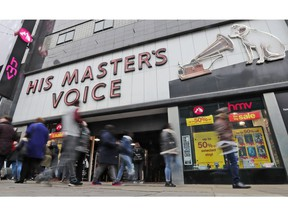 FILE - In this file photo dated Friday, Dec. 28, 2018, people pass a CD music and entertainment retailer HMV shop in London. HMV has been acquired out of administration by Canadian retailer Sunrise Records, it is announced Tuesday Feb. 5, 2019, safeguarding the future of nearly 1,500 staff, although it is understood that some unprofitable stores will close with immediate effect.