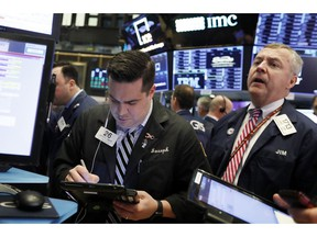 FILE- In this Feb. 5, 2019, file photo traders Joseph Lawler, left, and James Lamb work on the floor of the New York Stock Exchange. The U.S. stock market opens at 9:30 a.m. EST on Tuesday, Feb. 12.