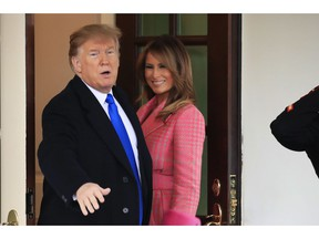 President Donald Trump with first lady Melania Trump, responds to reporters questions as he bid farewell to visiting Colombian President Ivan Duque and his wife Maria Juliana Ruiz Sandoval, outside the West Wing of the White House in Washington, Wednesday, Feb. 13, 2019.