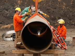 Enbridge workers weld pipe in Manitoba in 2018. Enbridge's Line 3 delay has heightened concerns Alberta may impose cuts for longer than its current target of year-end.