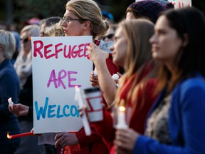 Supporters hold candles and signs during a Refugees Welcome rally held at the Alberta Legislature in Edmonton, Alta., on Tuesday September 8, 2015.