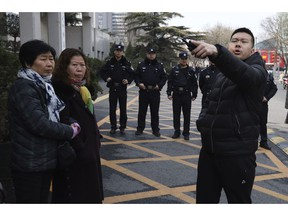 A Chinese security officer barks orders near relatives of passengers on board the missing Malaysia Airlines Flight 370 (MH370) who have gathered outside the Chinese Foreign Ministry demanding answers in Beijing, Friday, March 8, 2019. Friday marked the fifth anniversary of the disappearance of MH370, which vanished March 8, 2014 while en route from Kuala Lumpur to Beijing.