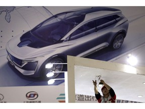 A worker installs lightings before the start of the Auto Shanghai 2019 show in Shanghai on Monday, April 15, 2019. This year's Shanghai auto show which starts Thursday highlights the global industry's race to make electric cars Chinese drivers want to buy as Beijing winds down subsidies that promoted sales.