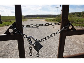 In this April 8, 2019, photo, the entrance to the coal-waste dump site is padlocked in Bokoshe, Okla. President Donald Trump's EPA has approved Oklahoma to be the first state to take over permitting and enforcement on coal-ash sites.
