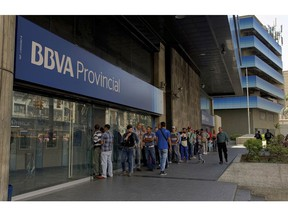 Customer line up outside a branch of Banco Provincial bank in Caracas, Venezuela, Monday, May 13, 2019. After 16 years of currency controls, the government is allowing its Bolivar to be exchanged on the floating market starting Monday, starting at 5,200 Bolivars per U.S. dollar.