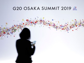 A woman walks past signage for the Group of 20 (G20) summit in Osaka, Japan, on Friday, June 28, 2019.
