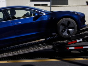 A worker unloads a Tesla Inc. Model 3 electric vehicle from a car carrier outside the company's delivery centre in California.
