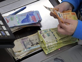 A cashier counts Argentine pesos bills at a supermarket in Buenos Aires on August 15, 2019.