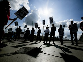 Demonstrators holds during a United Auto Workers (UAW) strike outside the General Motors Co. Flint Assembly plant in Flint, Michigan, U.S., on Monday, Sept. 16, 2019.