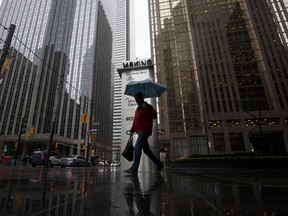 A pedestrian carries an umbrella while walking past signage for Home Trust Co., a subsidiary of Home Capital Group Inc., outside the company's headquarters in Toronto, on Thursday, May 4, 2017.