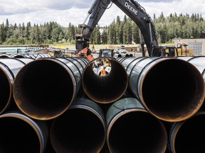 Pipe for the Trans Mountain pipeline is unloaded in Edson, Alta. on Tuesday, June 18, 2019.