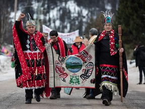 Chief Madeek (Jeff Brown), front left, hereditary leader of the Gidimt'en clan, and Wet'suwet'en Hereditary Chief Namoks (John Ridsdale), front right, carry a flag while leading a solidarity march after Indigenous nations and supporters gathered for a meeting to show support for the Wet'suwet'en Nation, in Smithers, B.C., on Wednesday January 16, 2019.