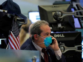 A trader wears a face mask on the floor of the New York Stock Exchange following traders testing positive for Coronavirus disease, in New York.